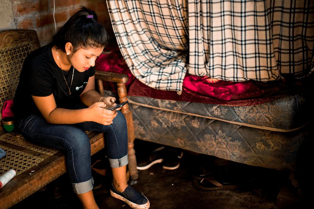 Adolescente mira su celular