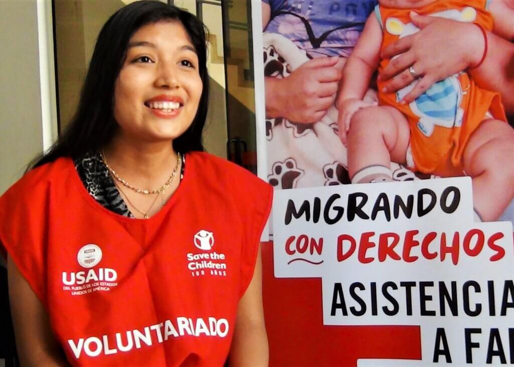 """Jennifer, voluntaria peruana de Save the Children. Sonriente, viste el mandil rojo de los voluntarios, con el logo de Save the Children, el de USAID y la palabra """"Voluntariado"""" en mayúsculas. Detrás se aprecia el banner del proyecto con el slogan """"Migrando con Derechos""""."""