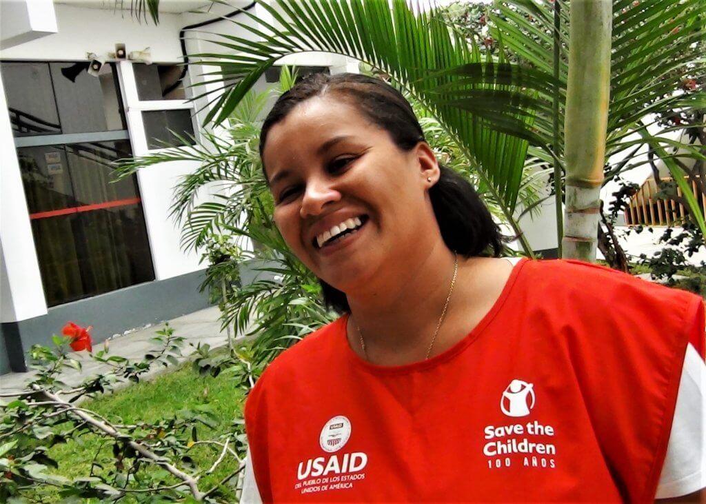 Leydy, voluntaria venezolana sonriendo. Viste un mandil rojo -uniforme del voluntariado- con los logos de Save the Children y USAID.