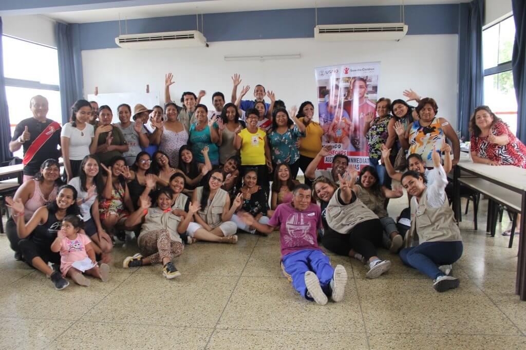 Grupo de voluntarios y voluntarias de la Asistencia Inmediata a Familisa Venezolanas en Emergencia y Riesgo de Save the Childrne y USAID en Piura. Sonrientes y levantando las manos