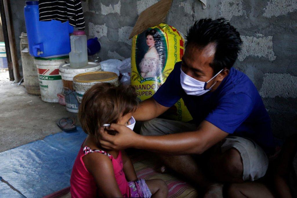 Padre pone mascarilla a niña