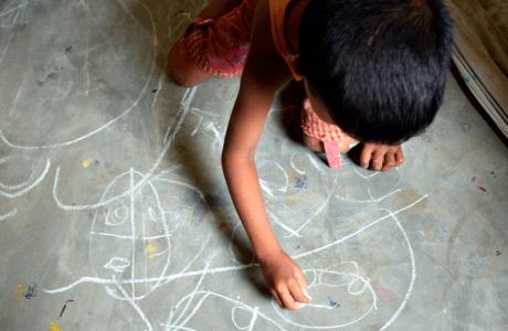 Niño dibuja con tiza sobre el suelo