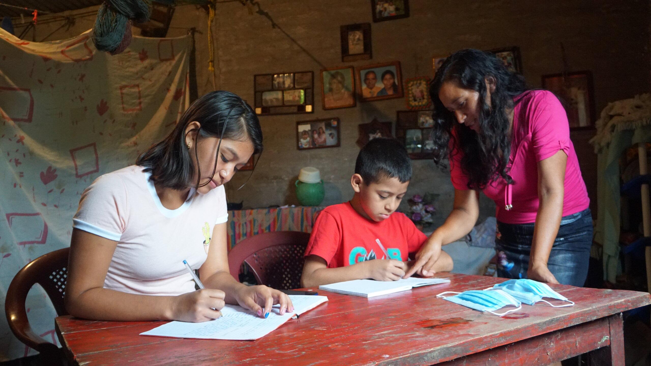 Mamá ayudando a niño y a adolescente con sus tareas. A un lado de la mesa tienen sus mascarillas.