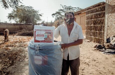 Hombre mayor usando mascarilla parado junto a kit de higiene