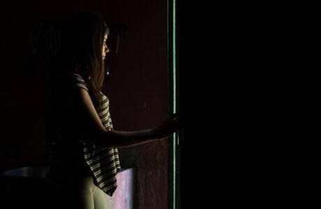 Adolescente en la oscuridad mirando una puerta