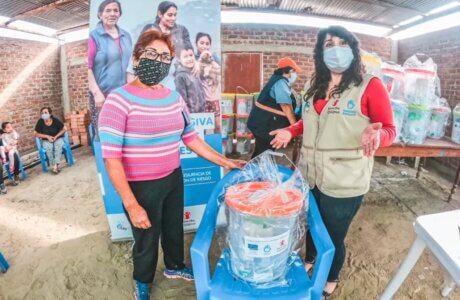 Staff de Save the Children entregando a una señora un kit de aseo para la prevención del COVID19. Ambas personas están usando mascarilla y en el fondo se aprecia el banner del proyecto.