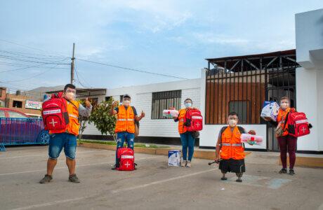 Lideres y lideresas del distrito de Ancón portan chalecos naranjas, mochilas de emergencia y botiquines